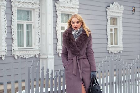 blonde girl in a purple coat with fur looks into the distance against the background of an old wooden house with platbands. 版權商用圖片 - 150407087