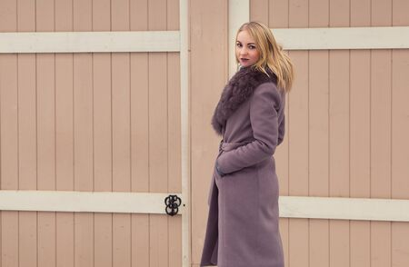 blonde girl in a brown coat with fur posing, smiling, looking to the side on a background of an old wooden door 版權商用圖片