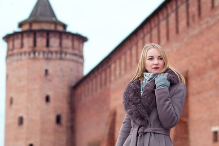 beautiful blonde girl in a brown coat with fur looks into the distance against the background of the Marinkina tower in Kolomna.