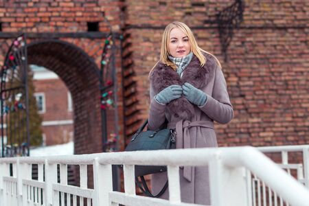 blonde girl in a brown coat with fur looks into the distance against a brick wall, arch standing on a bridge with a railing.