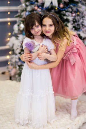 an older sister in a pink dress hugs her little girl in a white dress with a teddy bear. Christmas Archivio Fotografico