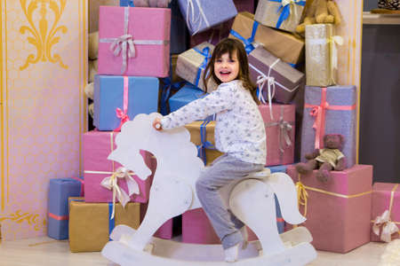 funny girl in white and gray pajamas rides a wooden rocking horse near a Christmas tree.