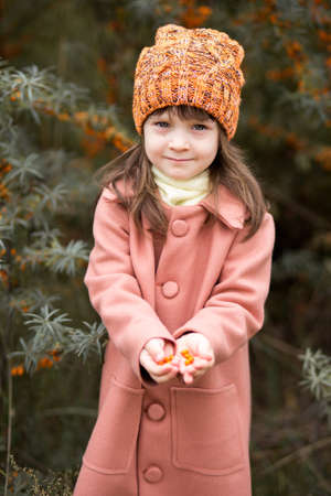vertical portrait of a cute girl in a brown coat and orange woolen hat. in the hands of a sea buckthorn berry. bushes in the background