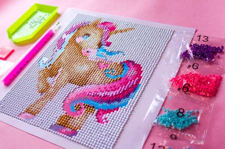 needlework set. diamond mosaic with unicorn on a pink background. Archivio Fotografico