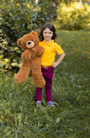 vertical photo. beautiful curly girl in a yellow t-shirt hugs a big brown teddy teddy bear. greenery around.