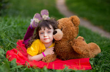 sad beautiful girl child in a yellow t-shirt lies on a red plaid and hugs a teddy bear.
