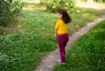 funny curly girl in a yellow t-shirt and burgundy pants is spinning around nature herself.