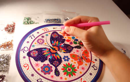 the hand holds the stylus and glues the mosaic. lesson diamond mosaic. set for gluing rhinestones on a butterfly picture. A lesson for the development of fine motor skills for children and adults. horizontal photo. the details Foto de archivo