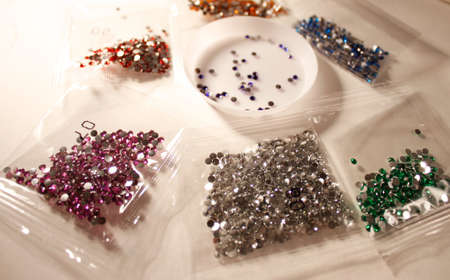 rhinestones and sequins in bags for practicing diamond mosaic on a white table. needlework set. horizontal photo of details Foto de archivo