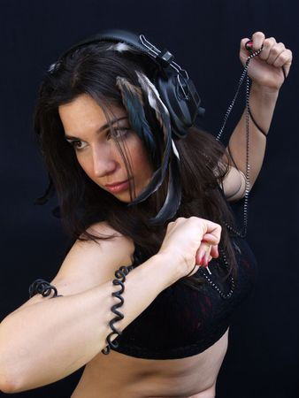 Young lady with headphones, wires coiling around her arms
