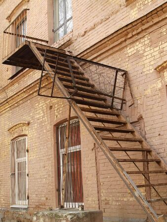 Rusty staircase outside a decayed building of pink bricks photo
