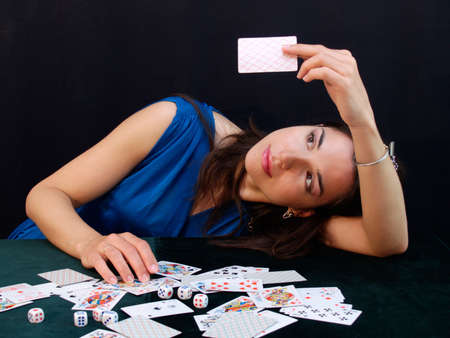 Young gambling woman contemplating over a playing card