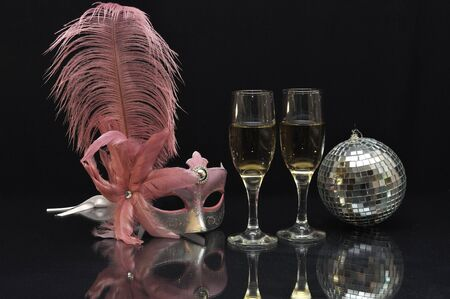 Pink mask with wine glasses and a mirror ball on black photo