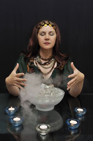 Lady with eyes closed practicing witchcraft on a black background