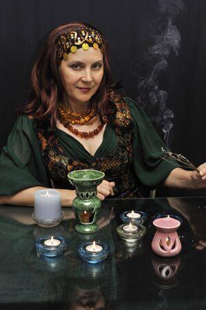 Glimlachende vrouw bij rituele acties op een zwarte achtergrond