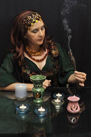 Femme magique avec brindilles de fumer sur un fond noir