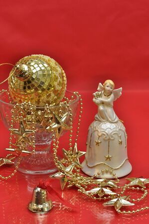 Golden christmas decoration with fancy bells on red background photo