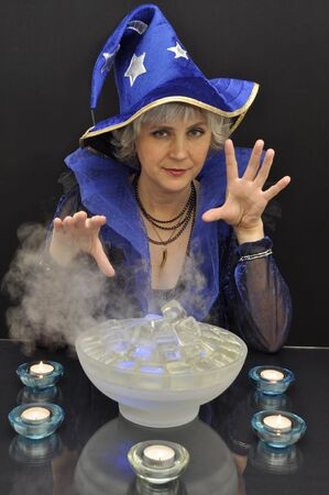 Witch in blue hat with magic crystals on black background Stock Photo - 11112976