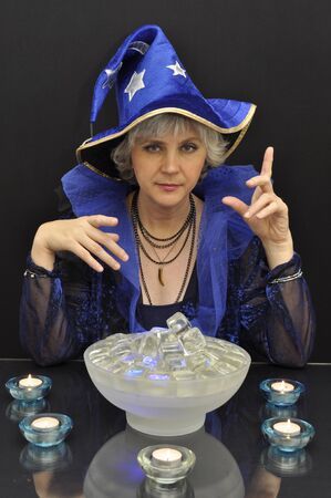 summoning: Witch in blue hat with magic crystals on black background