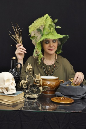 Magic woman in green hat with smoking twigs on black background Stock Photo