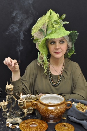 Magic Woman au chapeau vert avec des brindilles de fumer sur fond noir
