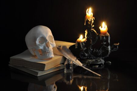 scull: Still life with scull, books and candles on black background Stock Photo