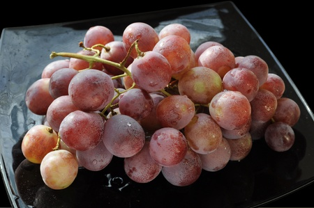 fascicle: Grape bunch on a black plate Stock Photo