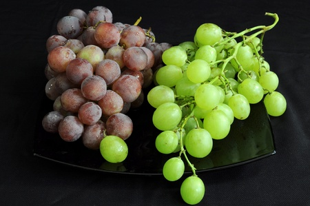 Two bunches of grape on a black plate Stock Photo - 11270416
