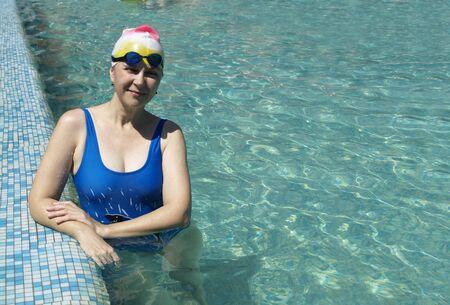 Lächelnde Schwimmerin entspannt auf dem Rand des Swimming-Pool Standard-Bild