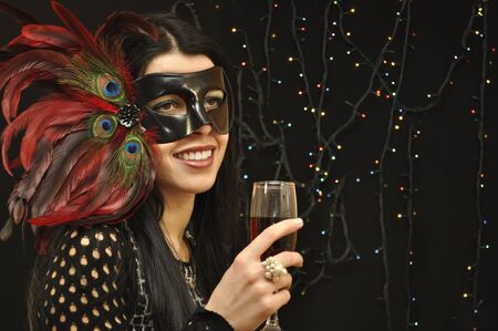 Smiling lady in fancy mask with a glass of vine on black background photo