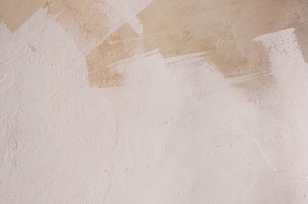 Background of partly painted stucco wall with layers of paint