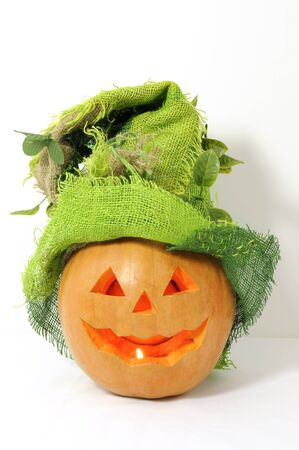 Pumpkin with green Halloween hat on isolated on white photo