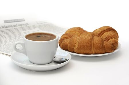 Cup of black coffee, croissants and breakfast accessories against a newspaper  photo