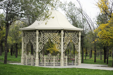 Beautiful arbor in autumn park surrounded by green grass photo