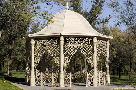 Beautiful gazebo in autumn park surrounded by trees and green grass photo