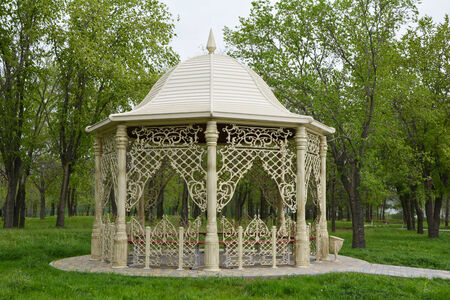 gazebo: Beautiful gazebo in spring park surrounded by trees and green grass Stock Photo