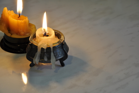 Two melting candles on a table surface background.