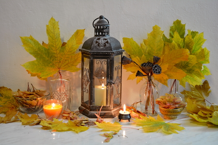 Still life with antique lantern and maple leaves