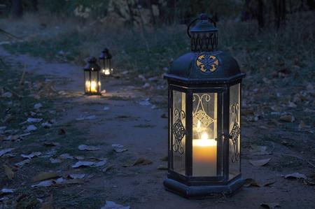 Antique lanterns on an autumn path in twilight darkness Stock fotó