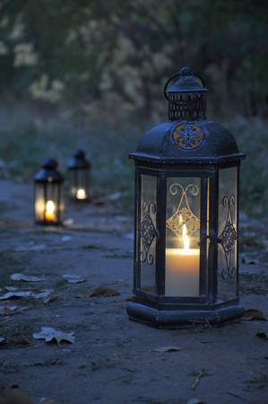 Antique lanterns on an autumn path in twilight darkness Stock Photo