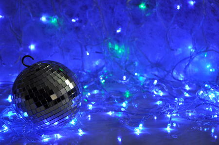 Disco christmas background with mirror ball and shining new year garland lights.