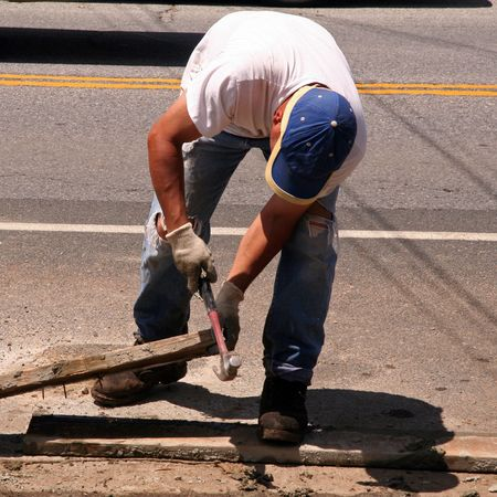 Construction Worker Hammering out a Nail