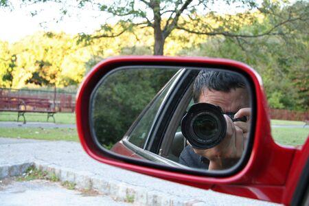 Paparazzi - Man taking photo from car Фото со стока