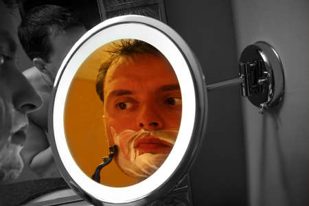 Guy Shaving in Mirror with his reflection photo