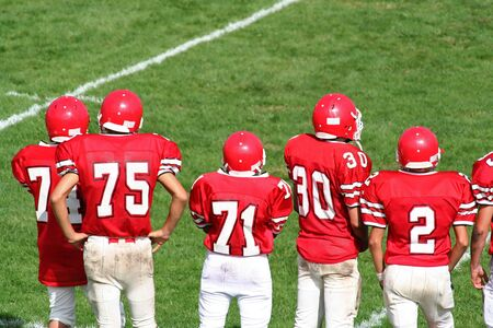 huddle: High School Football Team on Sidelines Stock Photo