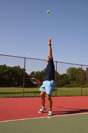 Young man serving tennis ball Фото со стока