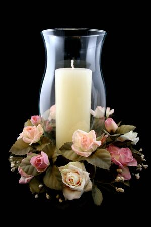 Holiday Candle and Flower Centerpiece on Isolated Black Background photo