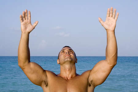 Young Man Meditating Near Ocean with Hand up in the Air Stock Photo