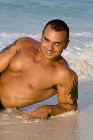 Tanned Male Model Lying Down on Beach photo