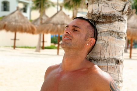 beach hunk: Young Man Relaxing on Beach Against a Palm Tree